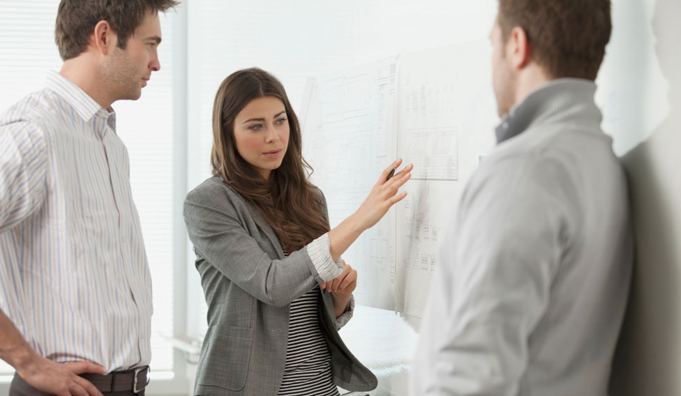 stock-photo-coworkers-discussing-at-whiteboard-156902491